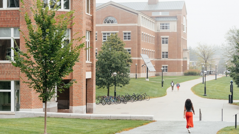 A student walks through campus on a cloudy day.
